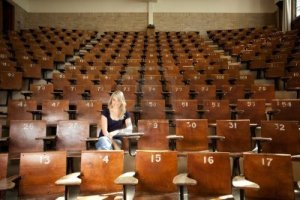 10559826-happy-blond-college-student-alone-in-large-lecture-hall